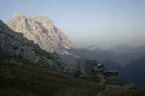 Rifugio Coldai in the foreground with Monte Pelmo in Golden sunlight in the distance