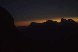 The peaks in the distance illuminated by the orange glow of sunset