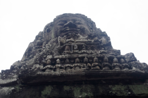 A large face above intricate carvings at the Bayon temple